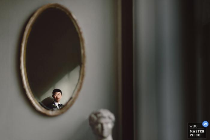 Le marié de New York City est reflété dans un miroir mural après qu'il a fini de se préparer le jour du mariage.