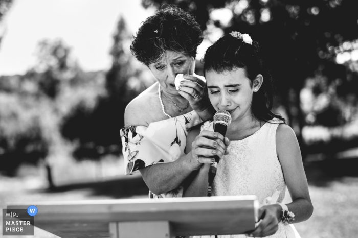 Lot-et-Garonne wedding photographer captured this black and white emotional image of a young girl getting assistance reading her wedding speech