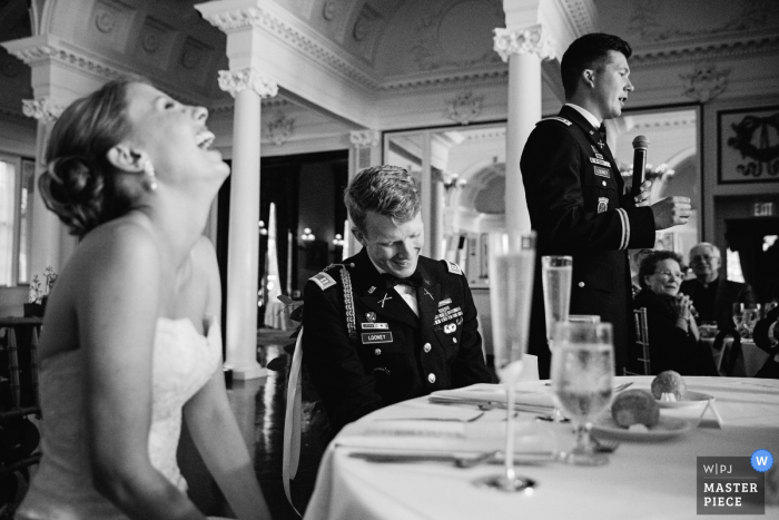 Saratoga wedding photographer captured this black and white photo of a bride and her serviceman groom laughing during speeches at their reception