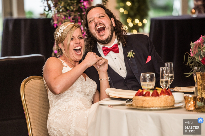 Cleveland wedding photographer capture this image of the bride and groom laughing hysterically at their reception