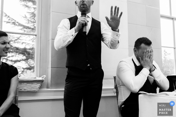 Nottinghamshire wedding photographer created this black and white photo of the groom covering his face in mortification as the best man gives his speech