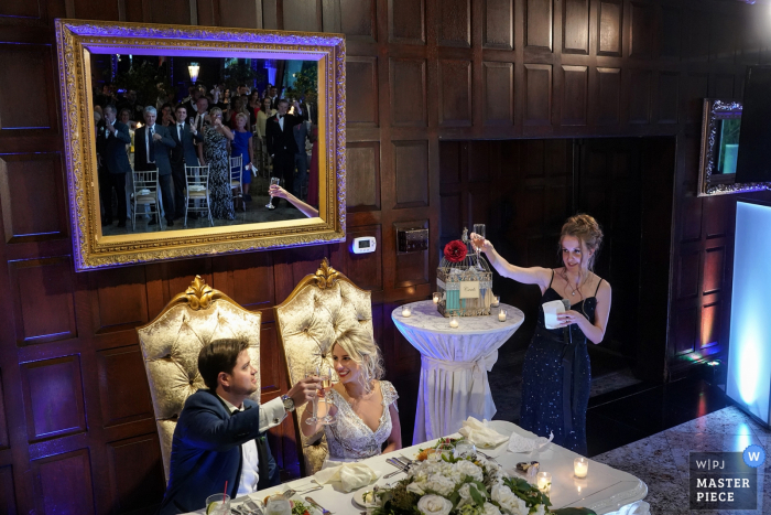 Bronx wedding photographer captured this photo of a bride and groom toasting in front of a wood paneled wall while listening to speeches from the bridal party