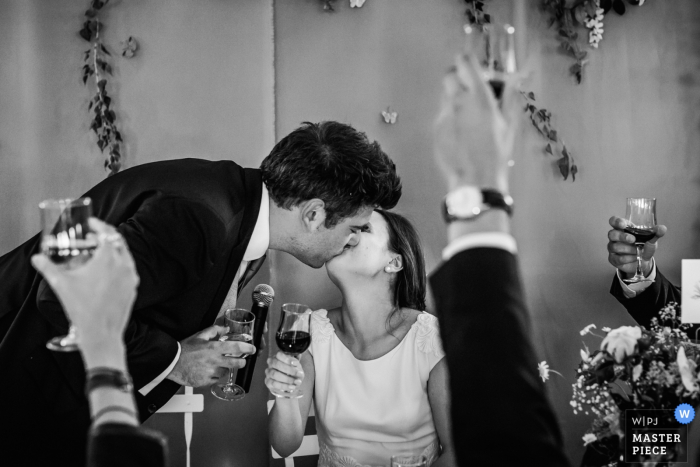 This black and white photo of a groom tenderly kissing the bride as onlookers raise their glasses in celebration was captured by a Montpellier wedding photographer