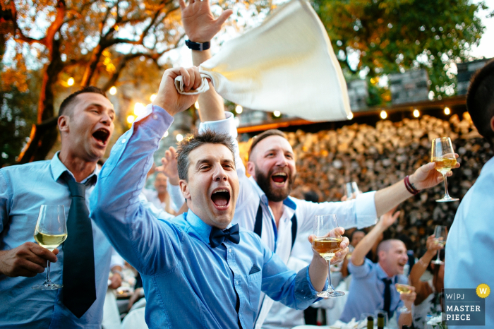 Rome wedding photographer captured this photo of three exuberant groomsmen toasting while listening to speeches at the wedding reception