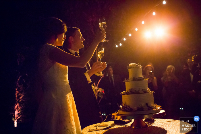 San Francisco wedding photographer captured this photo of the bride and groom toasting before slicing their wedding cake as a light casts and orange glow on the otherwise dark reception