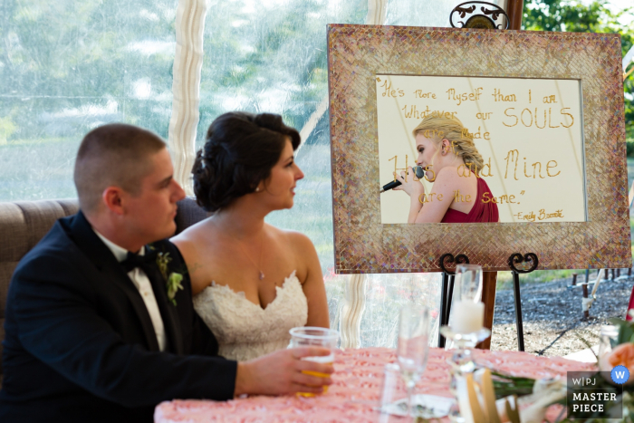 Maine wedding photographer captured this photo of the bride and groom listening attentively to the toasting speeches at their ceremony