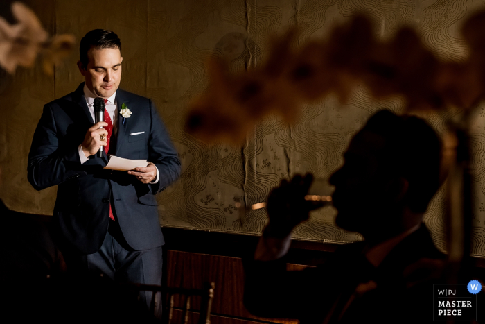 Boston wedding photographer captured this photograph of the best man reading his speech at the reception while the silhouette of the groom sipping champagne is in the foreground