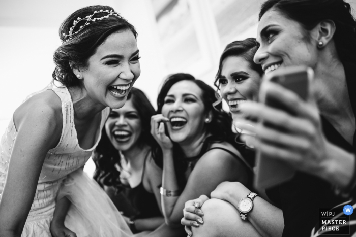 This black and white photo of the bride looking at phone images with friends was captured by a Cabo San Lucas wedding photographer