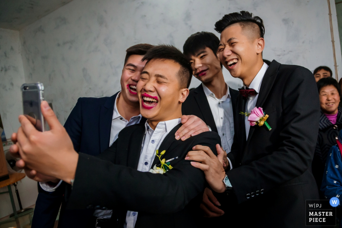 ChongQing wedding photographer captured this silly photo of the groom taking a selfie with his friends while wearing the brides lipstick