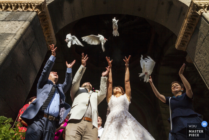 Armenia wedding photographer capture this photo of the bride and groom just as they release their doves after their wedding ceremony