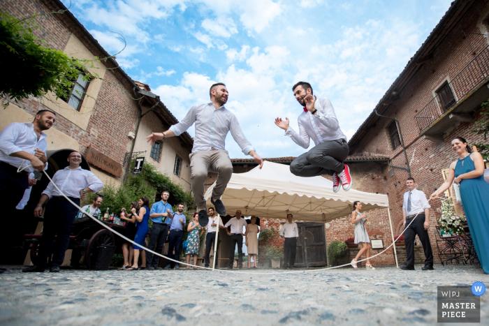 Der Cuneo-Hochzeitsfotograf hat dieses Bild von zwei Trauzeugen aufgenommen, die unter einem blauen Himmel abseilen