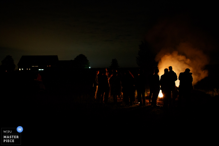 Der Hochzeitsfotograf von Noord hat die Silhouetten der Hochzeitsgäste festgehalten, die nachts vor einem Lagerfeuer stehen