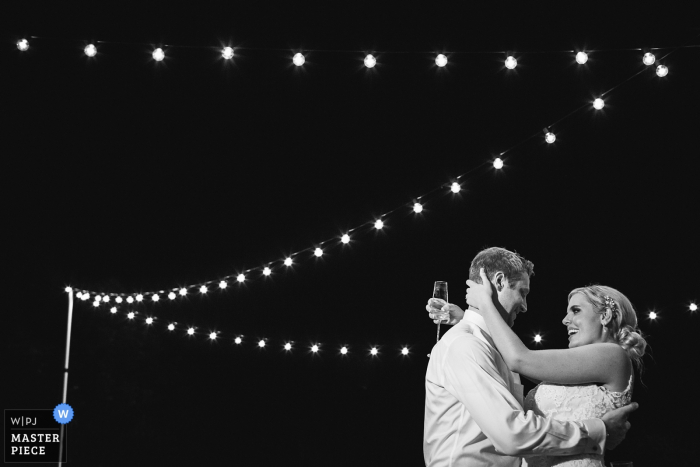 Charleston wedding photographer captured this black and white image of the bride and groom dancing at night under strings of twinkle lights