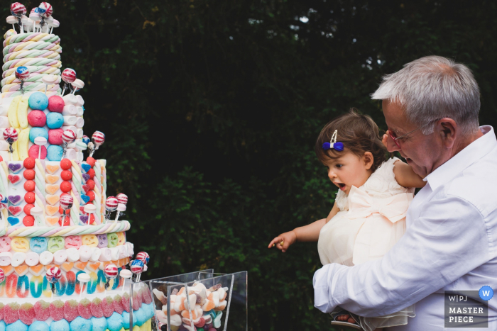 Paris wedding photographer captured the wonderment on a toddlers girl face while her grandfather shows her the candy covered wedding cake