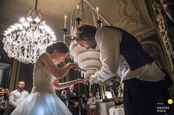 Paris wedding photographer captured this image of a bride and groom carefully cutting a slice out of their upside down wedding cake under a beautiful chandelier