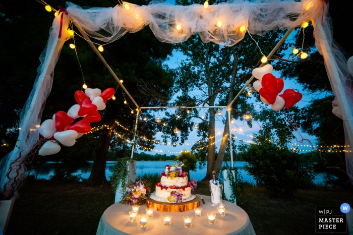 This detail shot of a cake sitting on a table in front of a lake with heart shaped balloons in the background was captured by a Brescia wedding photographer