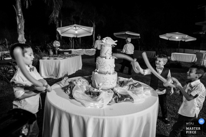 This black and white photo of little boys pretending to cut the cake with balloon swords was captured by a Sicily wedding photographer
