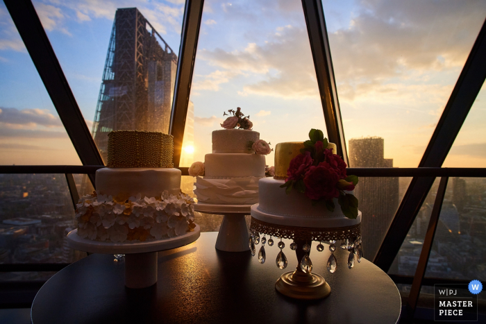 West Sussex wedding photographer captured this image of three wedding cakes displayed in front of a large glass window overlooking the city