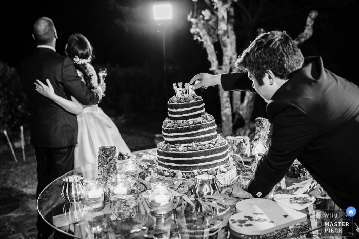 El fotógrafo de bodas de Libson creó esta foto en blanco y negro de los toques finales que se agregaron a la torta mientras que la pareja feliz posa para las fotos.