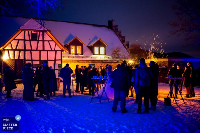 Le photographe de mariage d'Offenburg a capturé cette photo d'un paysage enneigé pendant que des invités déambulent à l'extérieur d'une villa et se blottissent autour d'un feu