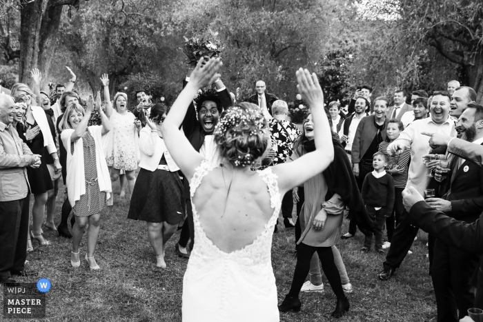 The bride throws the bouquet to an excited crowd in this black and white photo captured by a Paris wedding photographer