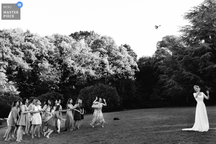 Paris wedding photographer captured this black and white photo of the bride tossing her bouquet in a wooded clearing