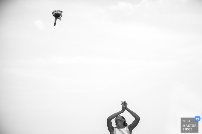 Lecco wedding photographer captured this black and white photo of the bride tossing her bouquet high in an overcast sky