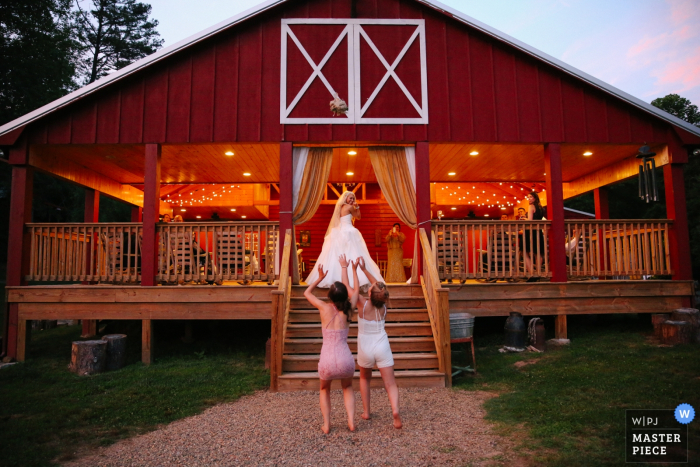 Knoxville wedding photographer captured this photo of two bridesmaids clamoring for the bouquet as the bride tosses it off the top step of a shelter house painted red and white to look like a barn