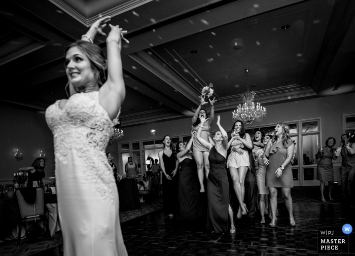 Charlotte wedding photographer captured this black and white photo of the bride tossing her bouquet and the group of women clamoring for it