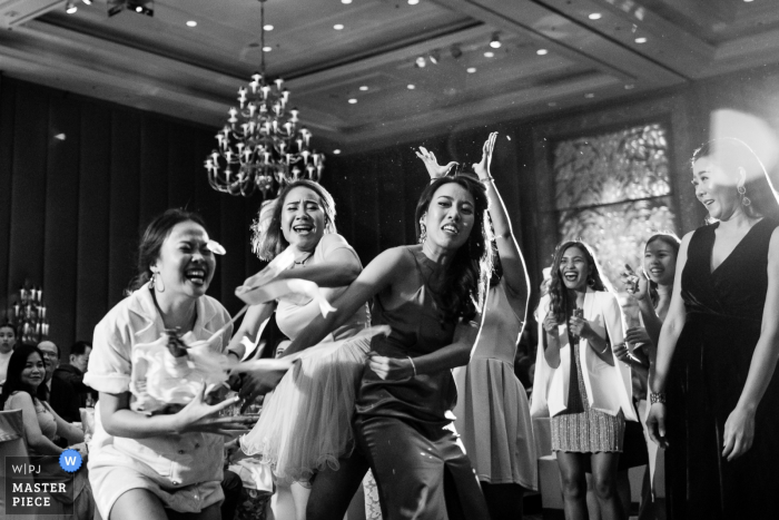 Nonthaburi wedding photographer captured this black and white image of a group of wedding guests competing fiercely to catch the bouquet