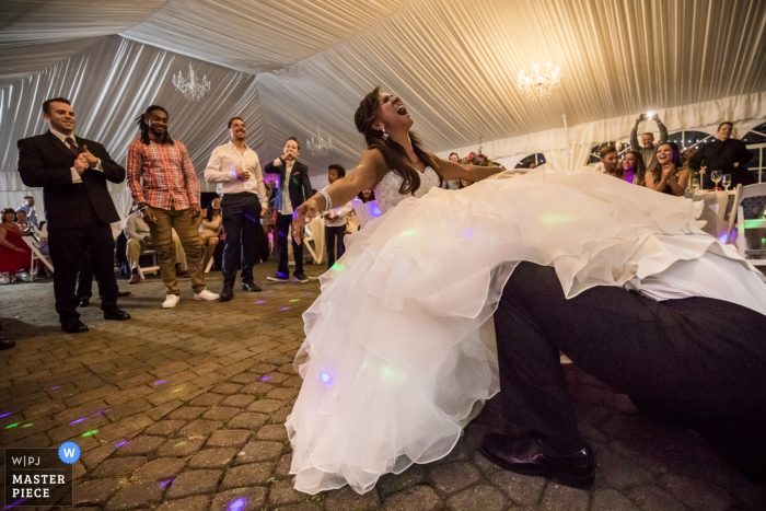 Tacoma wedding photographer captured this image of the groom lost in the brides gown while he retrieves the garter from her leg at their outdoor tent reception