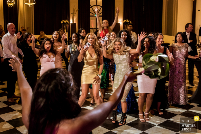 Rotterdam wedding photographer captured this image of a crowd of women waiting in rowdy anticipation for the bride to toss her bouquet