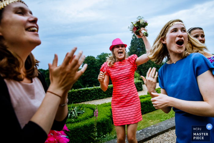 Flanders wedding photographer capture this image of a wedding guest celebrating her bouquet catch in a hedge lined garden