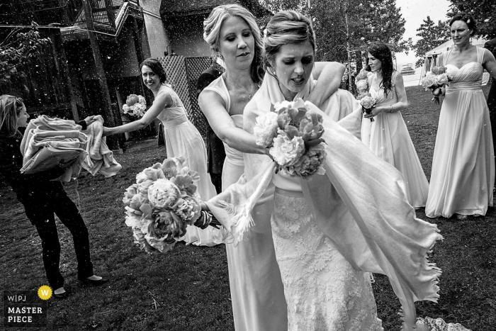 Una dama de honor ayuda a la novia a proteger su vestido de los elementos en una foto tomada por un fotógrafo de bodas de Lake Tahoe
