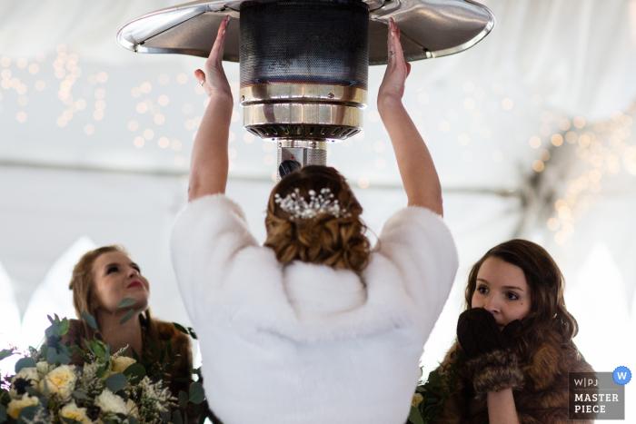 El fotógrafo de bodas de Missoula capturó esta imagen de invitados de bodas vestidos de manopla calentando bajo un calentador grande