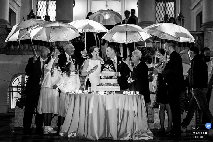 El fotógrafo de bodas de Tuscany capturó esta foto en blanco y negro de la novia y el novio cortando su pastel de bodas bajo un improvisado refugio paraguas