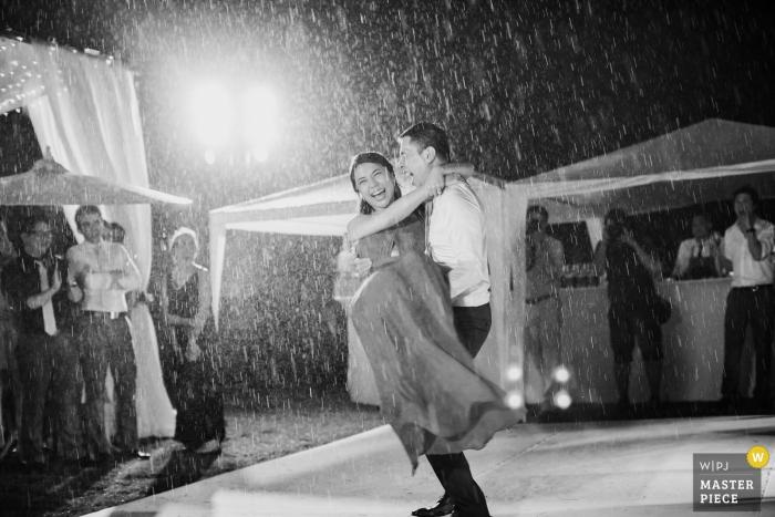 El fotógrafo de bodas de Phuket capturó esta foto en blanco y negro del novio que llevaba a su novia a través de la tormenta de lluvia después de su ceremonia