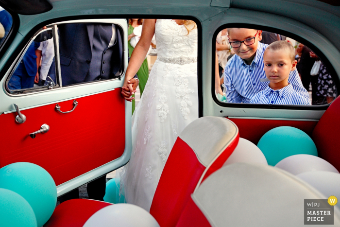 In this image, Reggio wedding photographer captured two small boys faces as they look through the window of a classic car at all the balloons inside while the bride gets ready to sit on the bright red leather seat