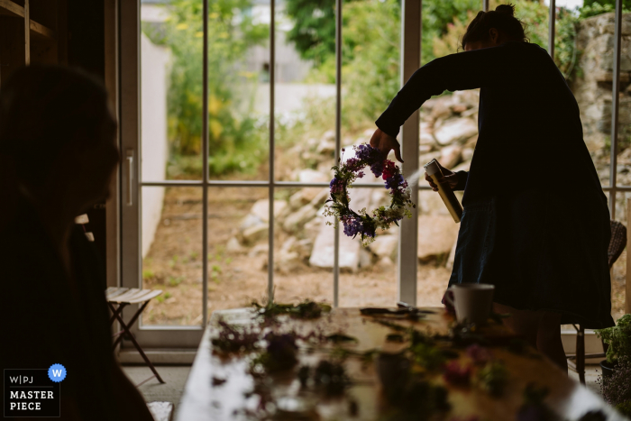 Grand Manchester wedding photographer captured this image of a florist putting some finishing spray on a flower crown