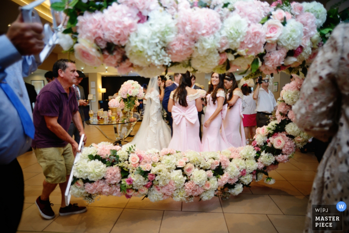 Hampshire wedding photographer captured this photo of bridesmaids clustered in pink dresses waiting for the florist to finish setting up the flowered covered arch