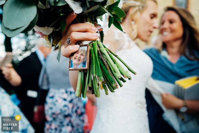 London wedding photographer captures this image of a charm containing a photograph of her grandmother attached to the brides bouquet