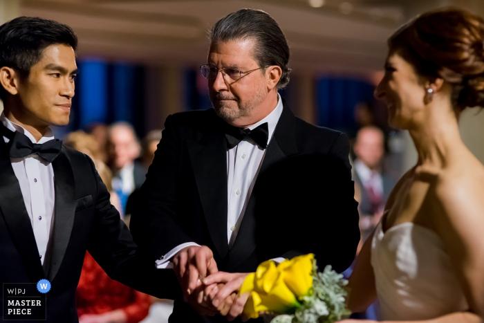 Le photographe de mariage de Boston a capturé le regard de confiance sur le visage des mariés lorsque le père de la mariée l'a remise à l'autel