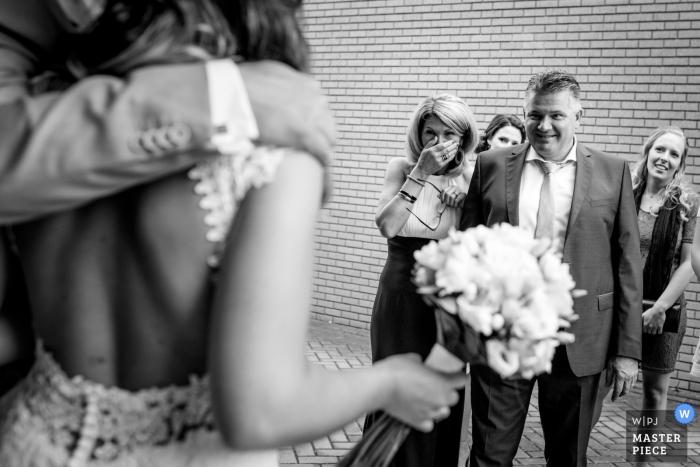 Overjissel, photographe de mariage, a capturé cette image des épouses de parents émotionnels qui regardent leur fille se faire prendre pour la première fois en tant qu'épouse