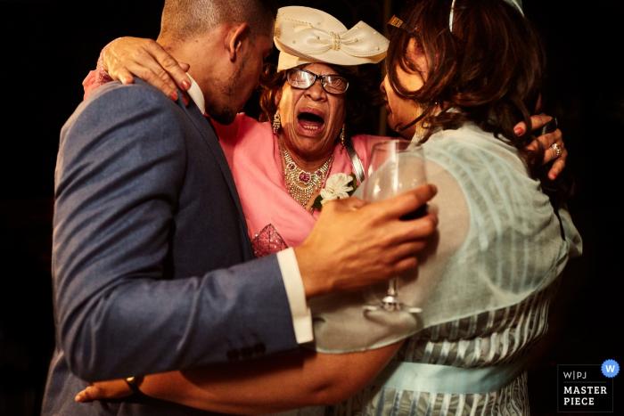 Le photographe de mariage de Florence a capturé cette image d'une épouse et d'un marié en train d'être pris dans un gros câlin par sa mère après qu'ils aient échangé leurs voeux