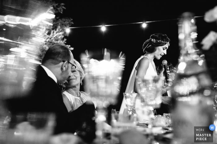 Le photographe de mariage de Portofino a capturé cette image en noir et blanc d'une épouse prononçant son discours tandis que ses parents souriaient à proximité