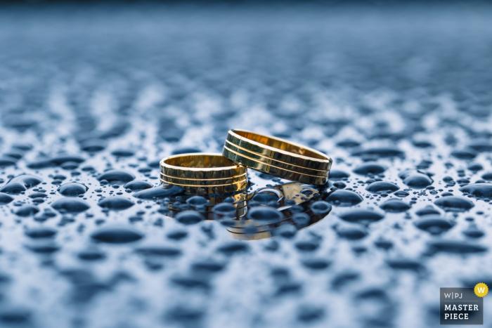 Un photographe de mariage de Basse-Silésie a capturé cette photo de détail des alliances posées sur une surface recouverte de gouttelettes d'eau