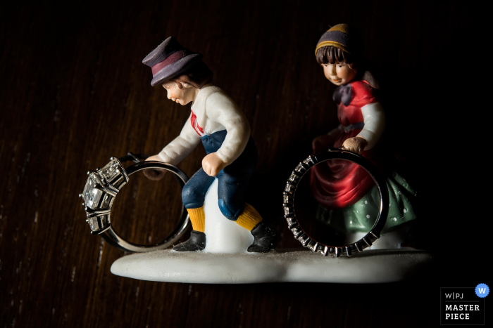 Boulder wedding photographer captured this photo using small statues as ring holders while photographing the bridal set