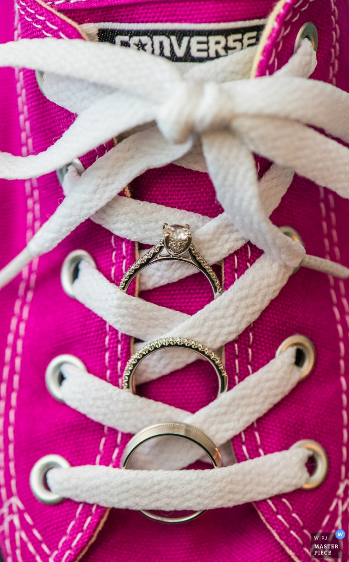 This detail shot of the wedding rings nestled in between the laces of hot pink converse tennis shoes was captured by a Charlotte wedding photographer