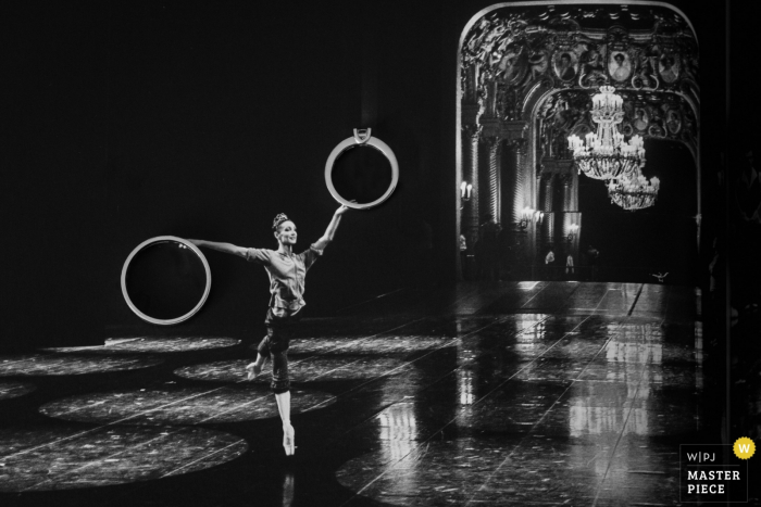 This black and white photo of the bride dancing ballet in the middle of an empty hall while holding life size representations of the bridal set was captured by a France wedding photographer