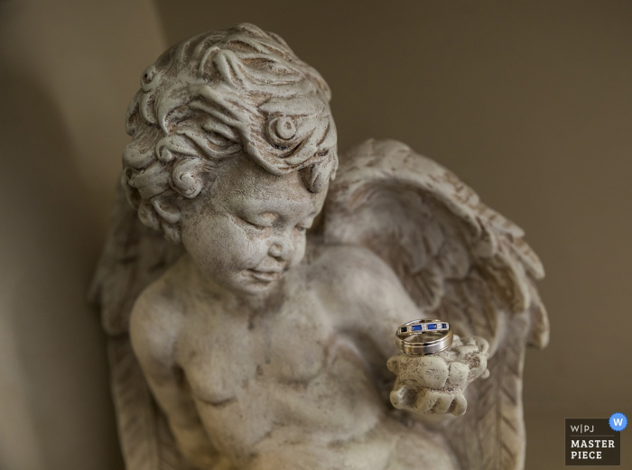 Tacoma wedding photographer captured this image of the wedding rings resting on the hand of a cherub statue